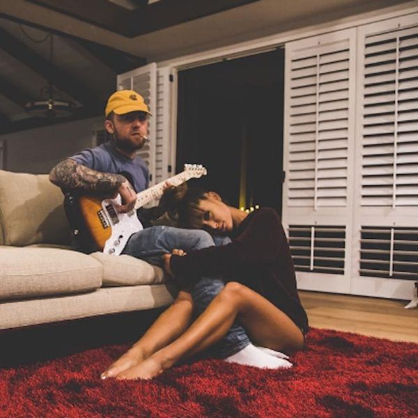 A imagem é uma foto dos cantores Mac Miller e Ariana Grande. Eles estão na sala de uma casa, em que Mac está sentado no sofá tocando uma guitarra, enquanto Ariana está sentada no tapete, abraçada com as pernas de Mac. Mac é uma homem branco, de cabelos castanhos claros raspados e barba castanha-clara rala; ele possui tatuagens pelo corpo e veste um boné amarelo, uma blusa azul clara, uma calça jeans e meias brancas. Ariana é uma mulher branca de cabelos castanhos claros, que estão presos em um coque; ela veste uma blusa preta de manga cumprida, não é possível ver seu shorts na imagem.