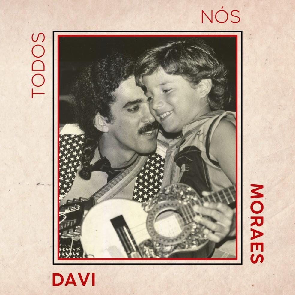 """Capa do disco Todos Nós. Na capa há uma borda na cor salmão. Do lado esquerdo lê-se em vermelho a palavra """"TODOS"""". No canto superior direito lê-se em vermelho """"NÓS"""". No canto esquerdo lê-se em vermelho """"Moraes"""". No canto inferior lê-se """"Davi"""". Dentro da borda há a fotografia de Davi Moraes ainda criança, abraçado ao seu pai Moraes Moreira. Moreira segura um cavaquinho. A foto está em preto e branco"""