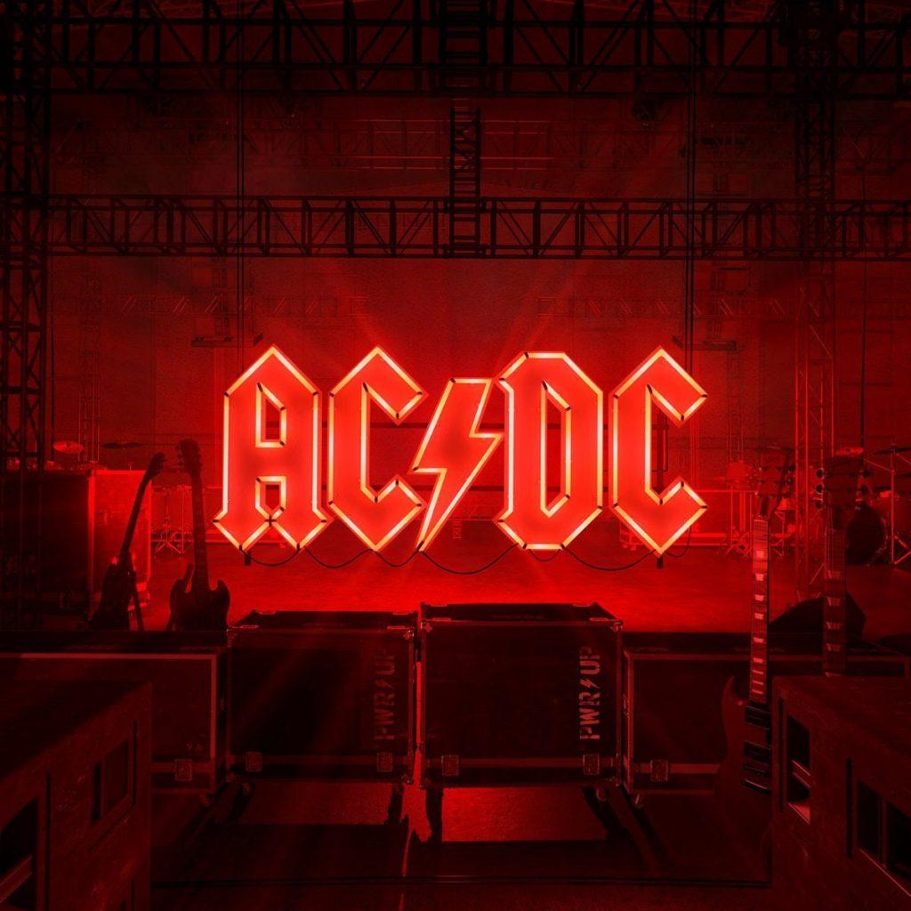 """A imagem é capa do álbum Power Up da banda AC/DC. A imagem é o fundo de um palco musical, com vários instrumentos e caixas de som. No centro da imagem há o nome da banda """"AC/DC"""" escrito como se fosse um letreiro na cor vermelha. Esse letreiro espalha luz e toda imagem é iluminada com uma luz vermelha."""