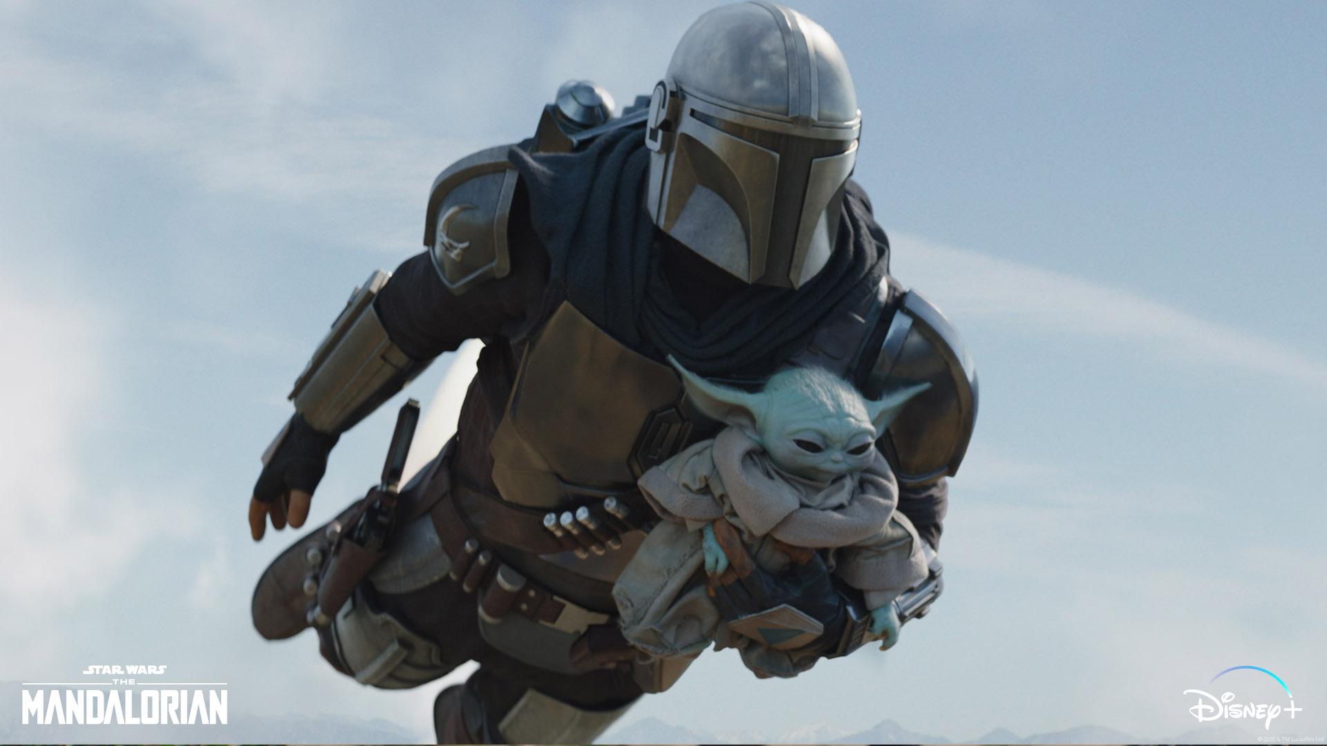 Cena da série The Mandalorian. Na imagem, vemos Din Djarin, vestindo a armadura mandaloriana e segurando Grogu em um dos braços. Ao centro, os dois voam pelo céu, ao fundo.