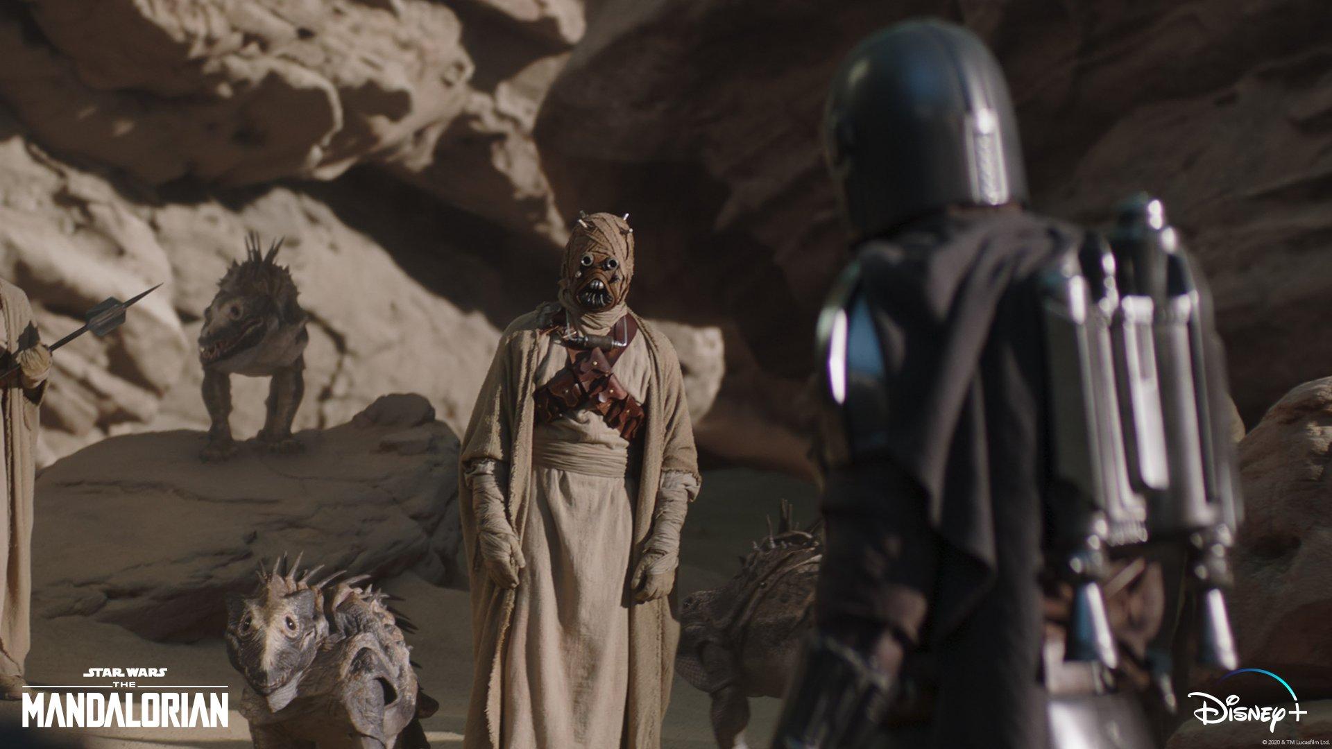 Cena da série The Mandalorian, em que Din Djarin, de costas à direita, conversa com uma criatura do Povo da Areia, que o encara, ao centro. Os dois estão próximos a pedras e há dois animais típicos do Povo, à esquerda.