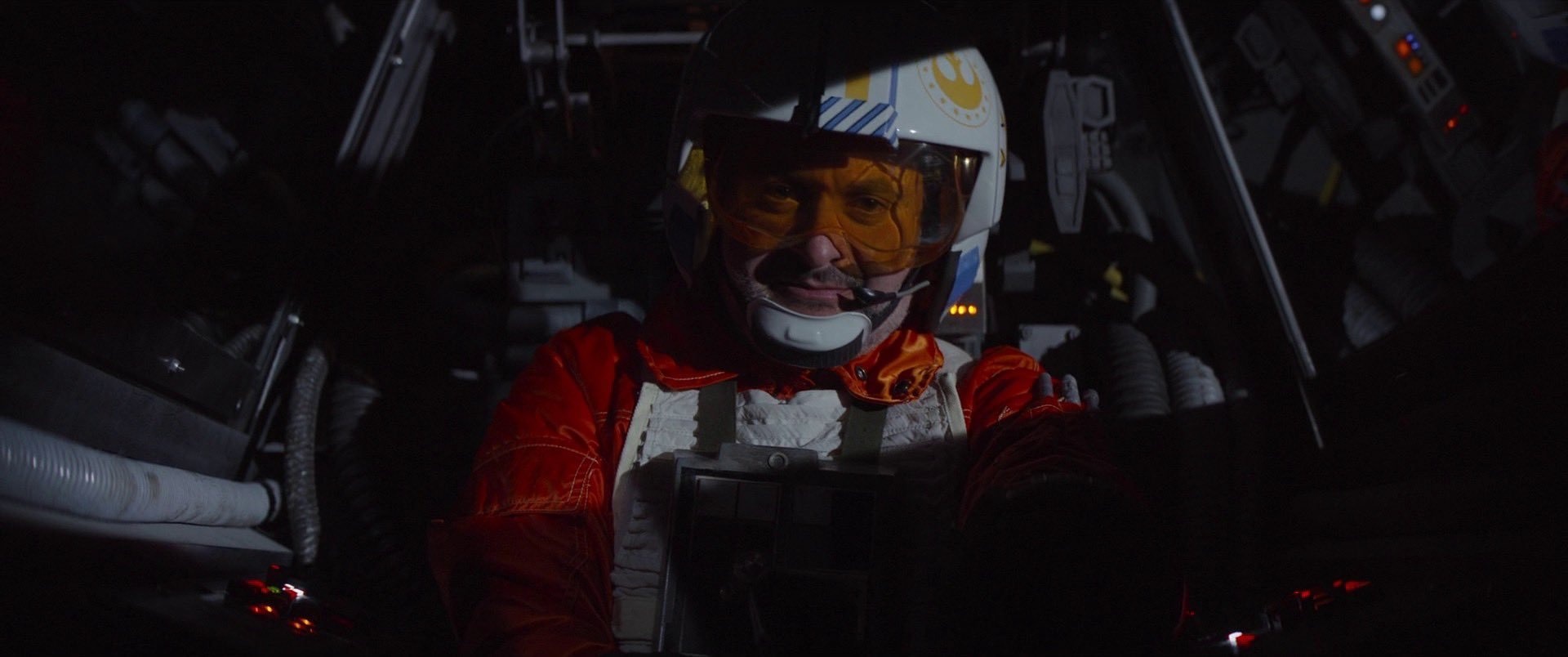 Cena da série The Mandalorian. Na imagem, há um piloto, interpretado por Dave Filoni, homem branco, vestindo um uniforme laranja e um capacete com o símbolo da Nova República. Ele está dentro de uma cabine da nave X-Wing.