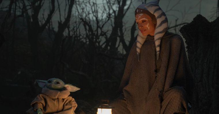 Cena da série The Mandalorian, que se passa de noite e em uma floresta. Na imagem, à esquerda, vemos Grogu, sentado e vestindo uma roupa marrom. À direita, a personagem Ahsoka Tano, sentada e vestindo uma roupa marrom, olha para ele. Entre eles, há uma luminária e, ao fundo, galhos de árvores retorcidos.