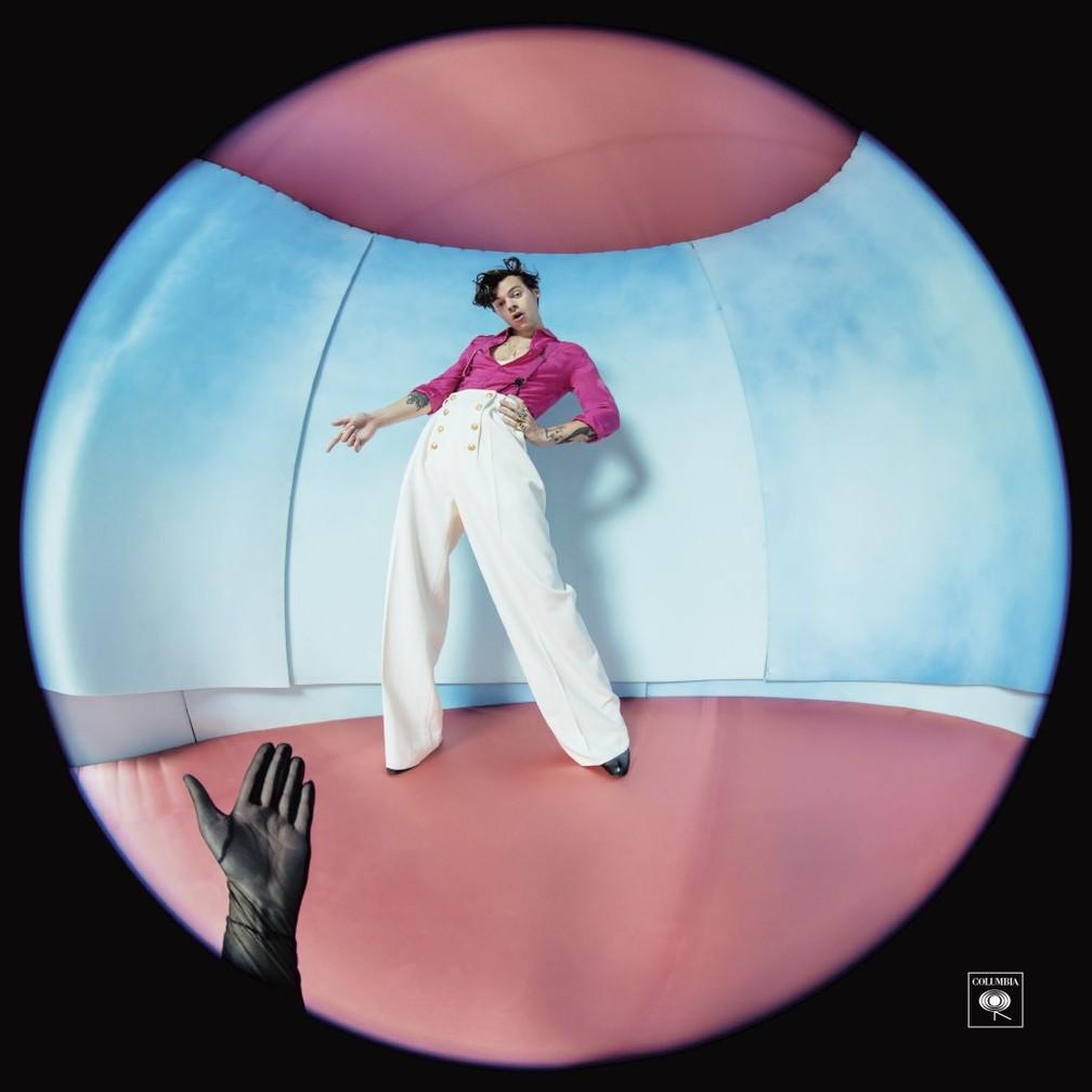 Capa do álbum Fine Line. Mostra Harry Styles, homem branco de cabelos curtos e pretos, em frente a uma parede azul clara. O teto e o chão são rosas e ele usa uma calça larga branca e uma blusa pink. A imagem é quadrada, mas ele aparece através de um círculo. As bordas são pretas e a frente tem uma mão usando luva preta.
