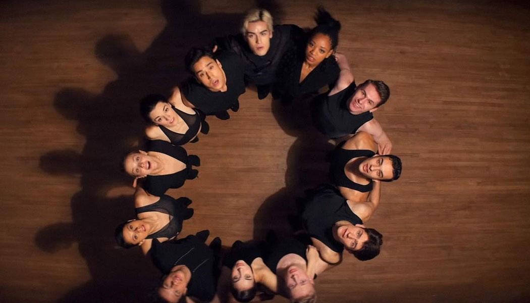 A imagem é de uma cena da série O Preço da Perfeição. A imagem é de 12 bailarinos se abraçando e olhando para cima. Todos eles vestem roupa preta e formam um círculo com seu abraço.
