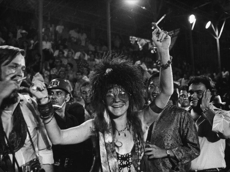 A imagem está em preto e branco. Janis Joplin, uma mulher branca, está no centro, com os braços levantados e um cigarro em uma mão. Ela usa regata, plumas na cabeça e pulseiras e colares. Ao seu redor, muitas pessoas curtem o carnaval do Rio de Janeiro.