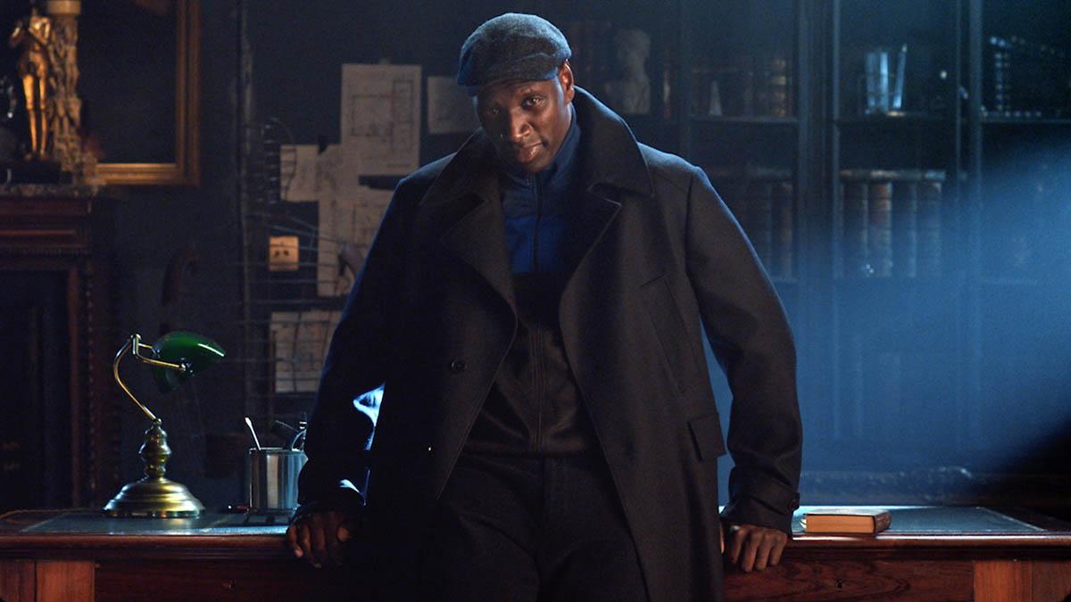 Foto promocional da série Lupin. Assane, um homem negro interpretado por Omar Sy, se apoia contra uma escrivaninha. Assane usa um casaco escuro e uma boina que se mesclam com o fundo. Uma única fonte de luz fria o ilumina diagonalmente. Atrás dele há uma estante com livros e alguns papéis presos contra a parede.
