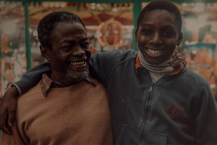 Uma foto antiga de Assane quando jovem, abraçando lateralmente seu pai, Babakar, interpretado por Fargass Assandé. Assane olha para a câmera, mas Babakar olha para o filho. Os dois sorriem. Assane usa uma jaqueta azul com detalhes em laranja e Babakar usa um suéter bege por cima de uma camisa xadrez. Eles parecem estar em algum tipo de celebração a céu aberto.