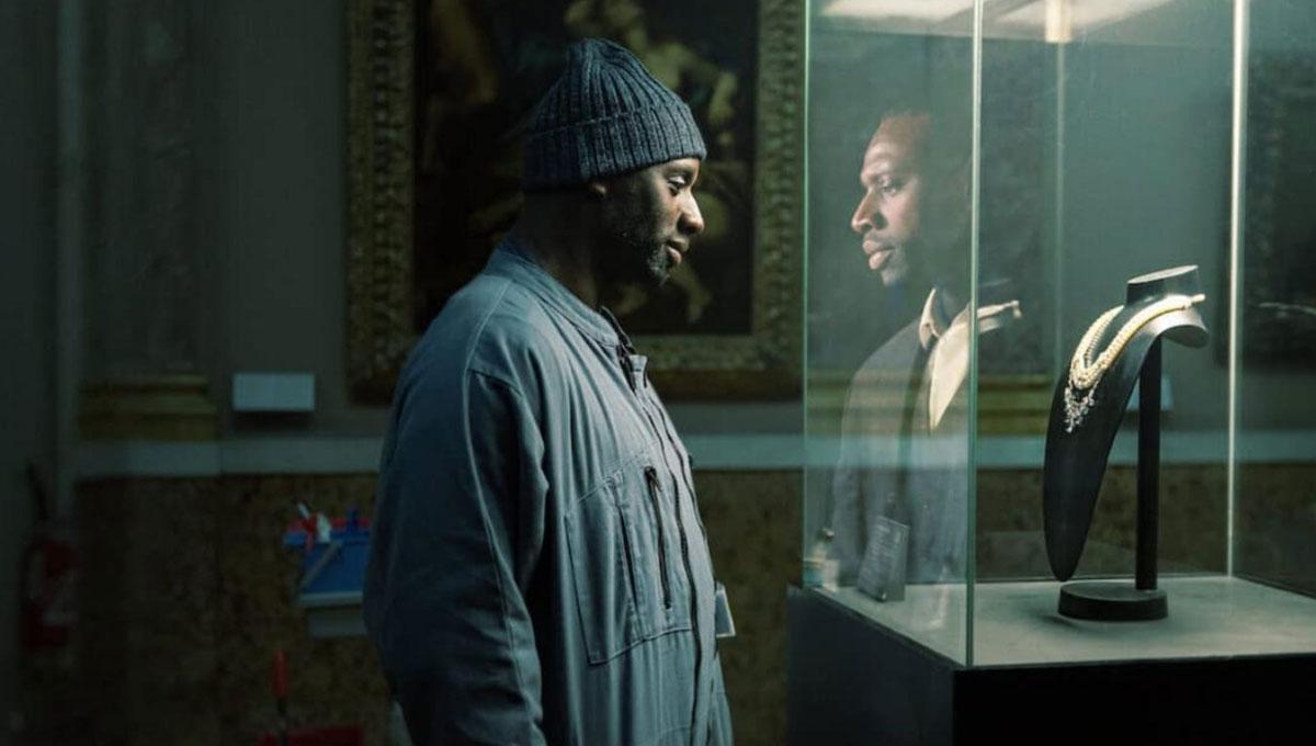 Foto promocional da série. Assane, disfarçado de faxineiro dentro do Louvre, olha para um colar em exposição protegido por uma caixa de vidro. Ele usa um macacão cinza e uma touca azul escura. Na reflexão do vidro, ele aparece usando um terno e colete pretos por cima de uma camisa branca. Atrás dele há algumas pinturas em exposição.