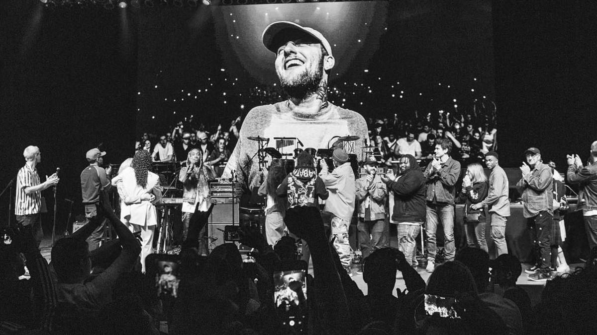 A imagem é uma fotografia do show de tributo para Mac Miller. Na imagem, podemos ver, em cima do palco, um telão com uma foto de Mac. No palco do show, estão vários cantores e equipe aplaudindo em direção ao telão; e, em frente, é possível ver a plateia aplaudindo, com as mãos para o alto. A imagem está em preto e branco.