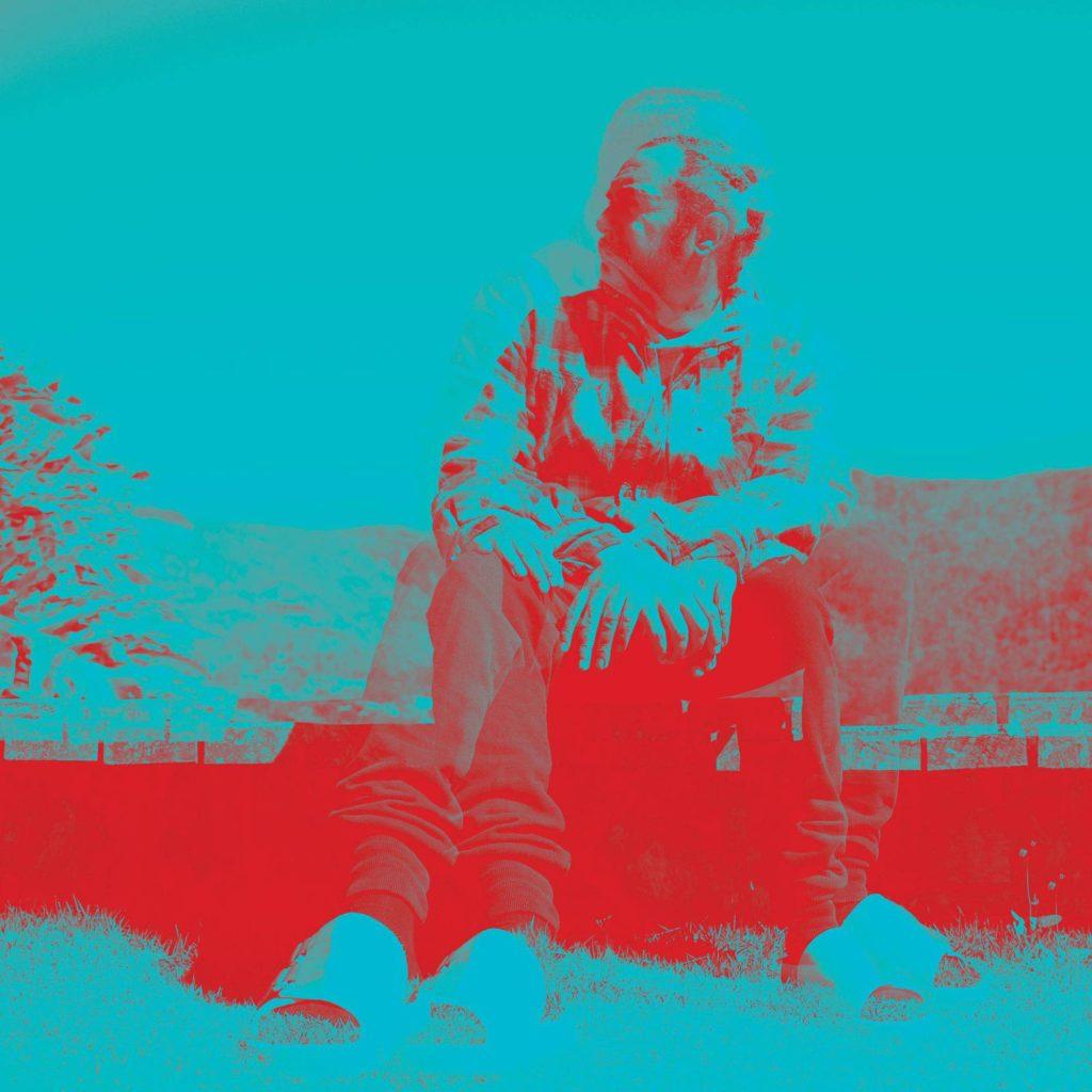A imagem é capa do álbum Assim Tocam os MEUS TAMBORES do rapper Marcelo D2. A imagem é uma fotografia do cantor sentado e há um campo no fundo. A imagem possui um efeito que deixa ela nas cores azul e vermelho.