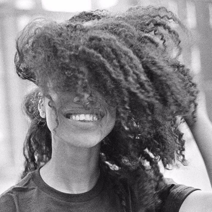 Capa do álbum autointitulado da artista Lienne La Havas. A imagem é composta apenas por uma fotografia da artista, em preto e branco. Ela aparece dos ombros para cima, e seu cabelo cacheado cobre parte do seu rosto, aparecendo apenas seu sorriso. Ela também usa um piercing de argola simples no meio das narinas e usa uma camiseta escura. A mão esquerda de Lienne La Havas segura o cabelo, na altura da orelha. Ela está levemente à esquerda da imagem e de frente para a camêra.