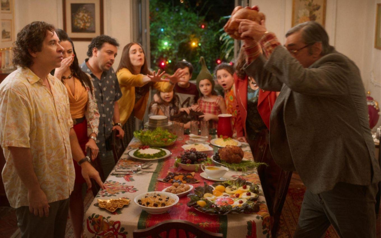 Imagem do filme Tudo Bem no Natal que Vem. Nela vemos uma família com 10 pessoas reunidas em volta de uma mesa de jantar onde está sendo servido a ceia de Natal. Tio Vitor, um homem branco, meia idade, grisalho, vestindo um terno cinza, está segurando o peru acima da cabeça enquanto os outros personagens o olham de forma espantada e Laura, mulher branca, morena, com blusa amarela, se inclina para ele de forma espantada.