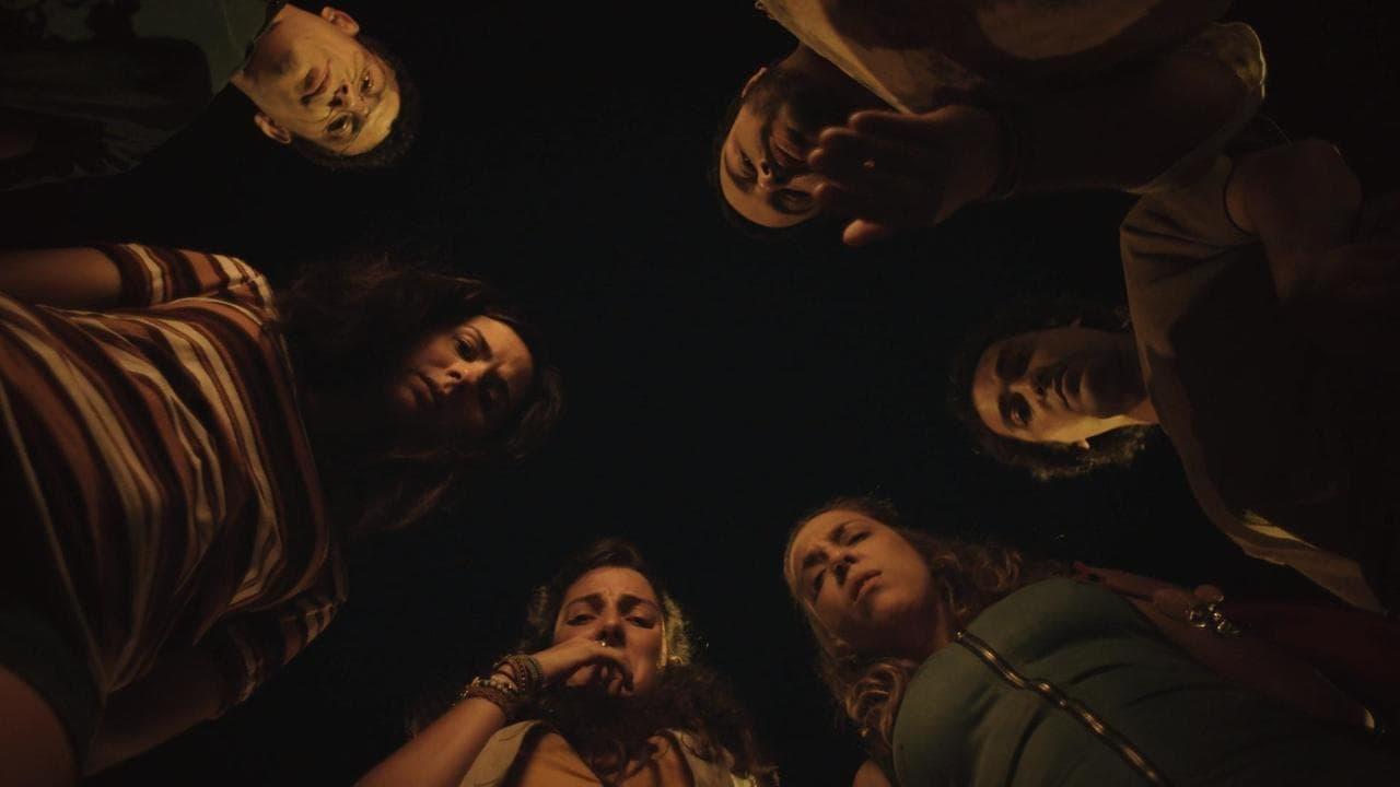 A imagem é de uma das cenas da série Shippados. A imagem foi tirada de baixo para cima. Nela, os personagens estão em roda olhando para baixo, em direção à câmera. Nesse círculo estão, nessa ordem, os personagens de Luis Lobianco, Eduardo Sterblitch, Júlia Rabello, Clarice Falcão, Tatá Werneck e Rafael Queiroga.