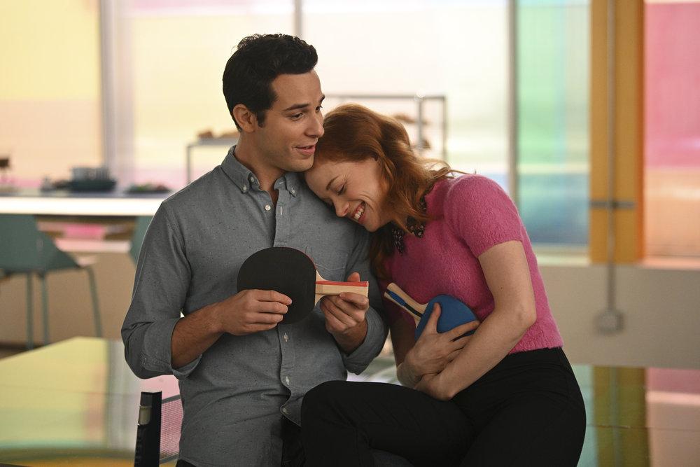Imagem da série Zoey e sua Fantástica Playlist. Ao centro, Zoey está sentada numa mesa da empresa que trabalha ao lado de Max, seu melhor amigo. Ele é branco, seus cabelos são curtos e escuros e ele usa uma camisa social azul acinzentada. Zoey está ao lado, sorrindo, com a cabeça deitada nos ombros do amigo. Ela usa uma uma blusa rosa e uma calça preta. Os dois seguram raquetes de pingue pongue, e Max a usa como um violão.