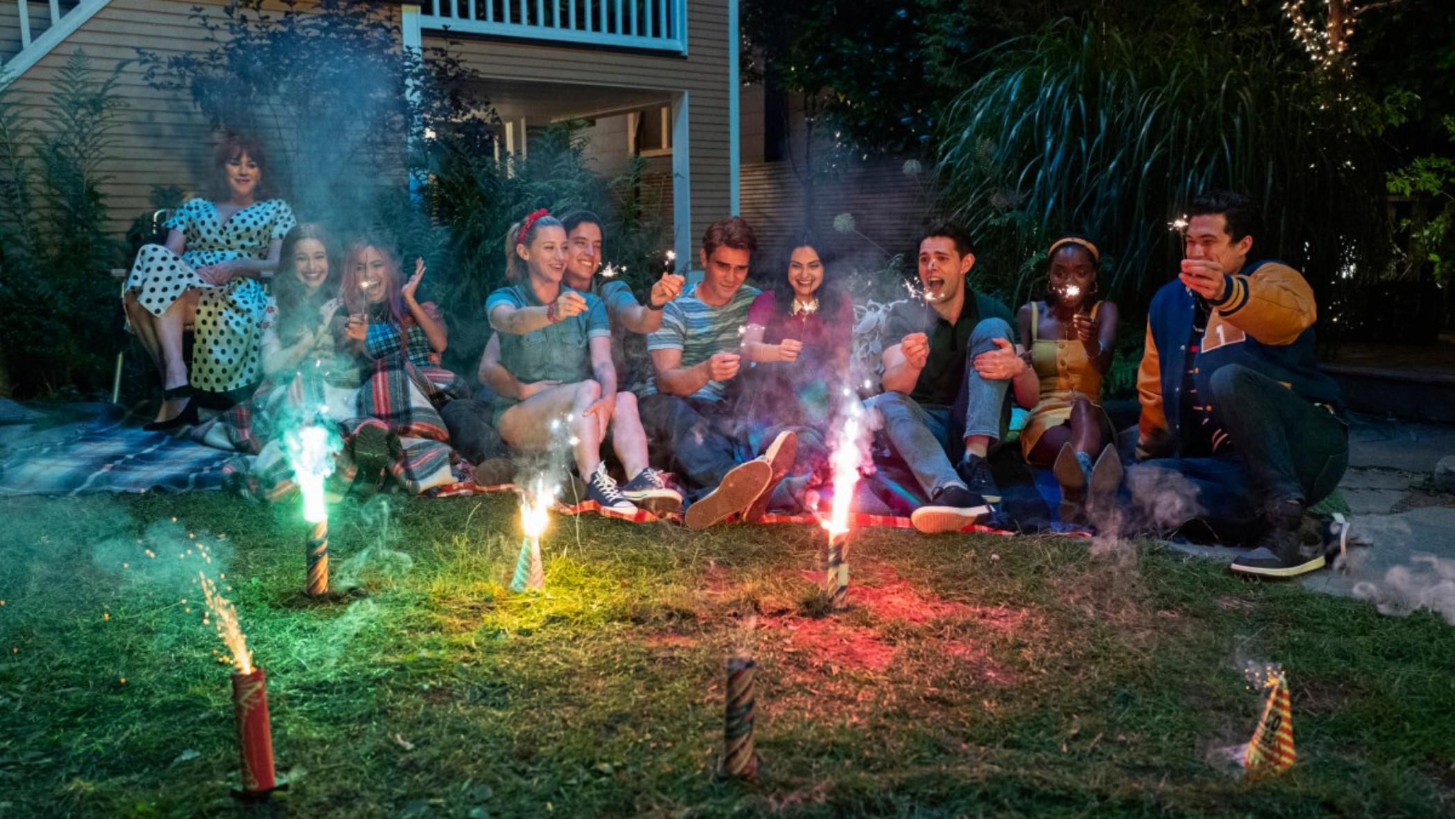 Cena da cena Riverdale. Na cena, vemos uma porção de pessoas sentadas num gramado, sorrindo, enquanto fogos de artifício queimam à frente deles.