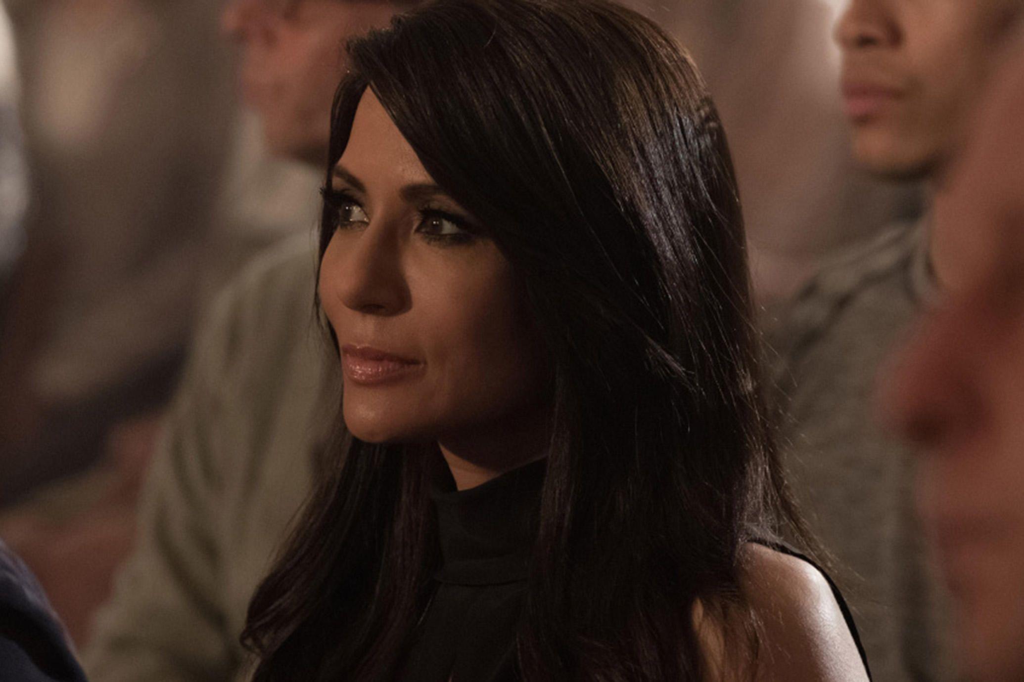 Cena da cena Riverdale. Na cena vemos Hermione Lodge, uma mulher latina de meia idade. Ela tem a pele clara, e os olhos e cabelos pretos.