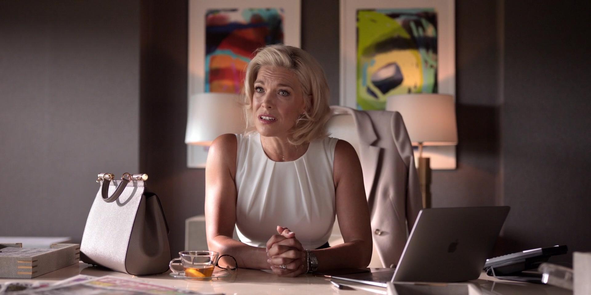 Cena da série Ted Lasso. Na cena vemos Rebecca, uma mulher branca, na casa dos 50 anos, de cabelos loiros platinados e vestido branco. Ela está sentada à sua mesa, com as mãos dadas e uma expressão de dúvida e descontentamento no rosto. Na mesa, estão seu laptop branco, sua bolsa branca e mais uma porção de objetos fora de foco. Ao fundo, também desfocados, estão dois quadros.