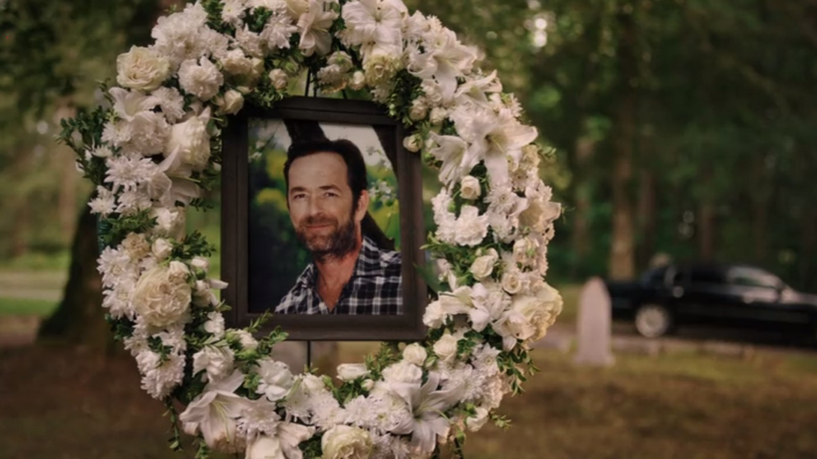 Cena da cena Riverdale. Vemos uma coroa de flores branca, e no centro dela está o retrato de Fred Andrews, um homem branco de meia idade, cabelos e barba preta, ele sorri na foto. O cenário é um cemitério com muitas árvores e grama verde.