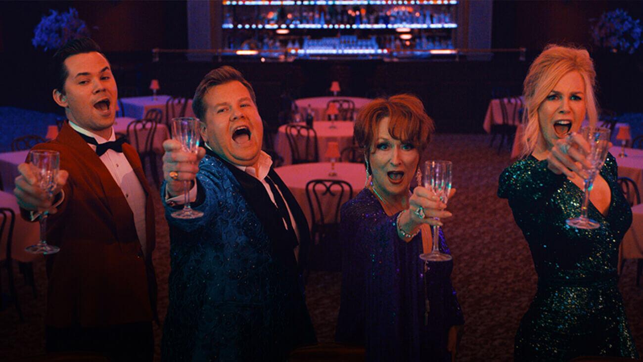 Cena do filme A Festa de Formatura. Mora os personagens, da esquerda para a direita, de Andrew Rannells de terno vermelho e camisa branca, James Corden de terno azul, Meryl Streep de vestido roxo e Nicole Kidman de vestido verde. Todos eles seguram taças e cantam.