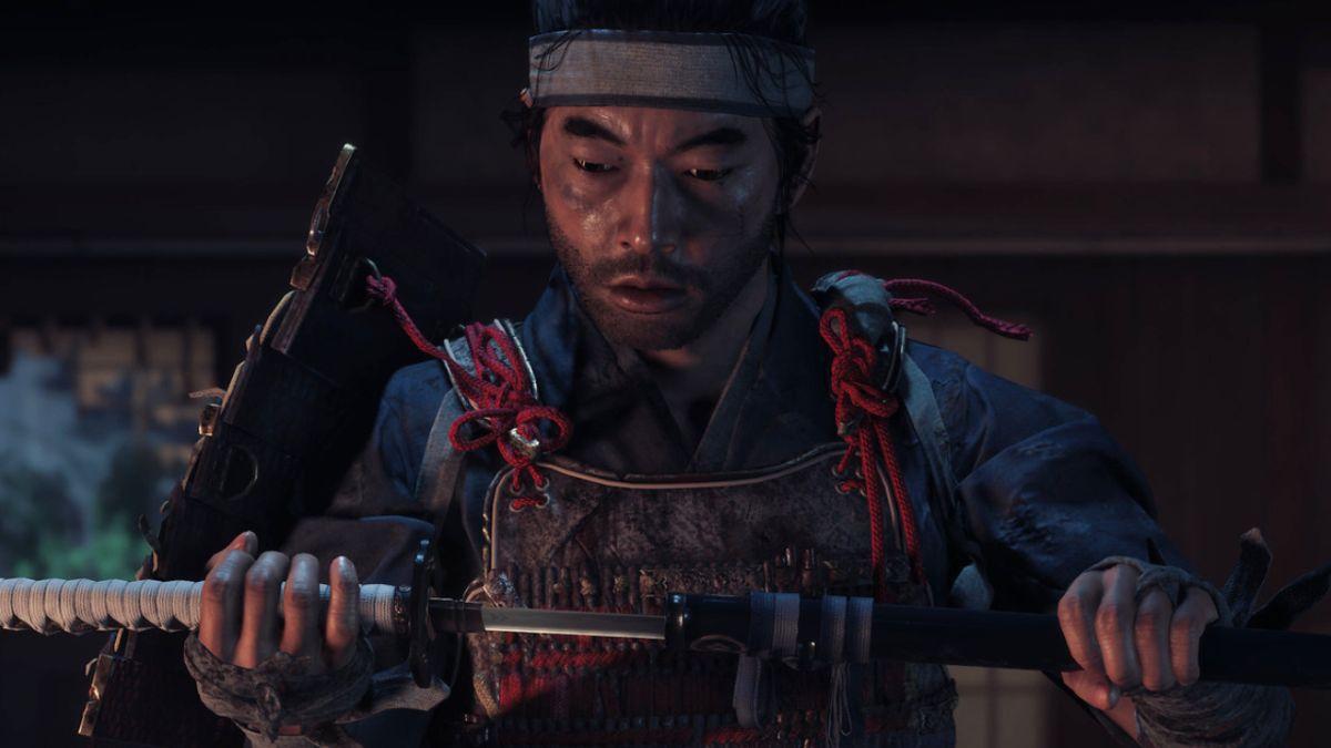 Cena do jogo Ghost of Tsushima. Jin olha para sua espada, desembainhada pela metade. Ele usa uma armadura de samurai danificada com peças faltando e uma bandana branca. Ele está dentro de uma casa e atrás dele há uma janela quebrada que dá para o exterior noturno.