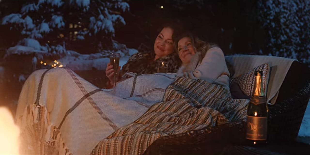 Cena da série Amigas Para Sempre, print de tela, as personagens Tully e Kate estão juntas debaixo de um cobertor em uma espécie de sofá ao ar livre durante a noite. Tully está bebendo vinho. A foto tem pouco contraste.