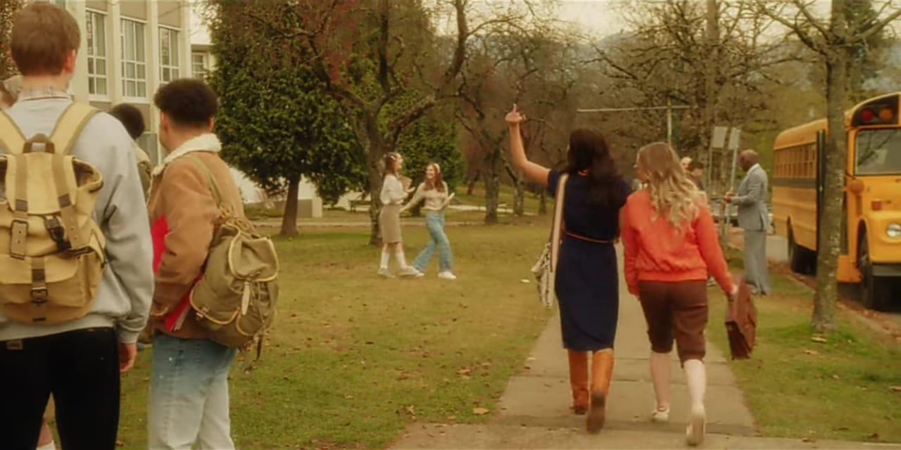 Cena da série Amigas Para Sempre, print de tela, Tully e Kate, duas mulheres brancas, ainda adolescentes caminhando em frente à escola, as duas estão de costas e Tully mostra o dedo do meio. A foto tem a temperatura mais quente