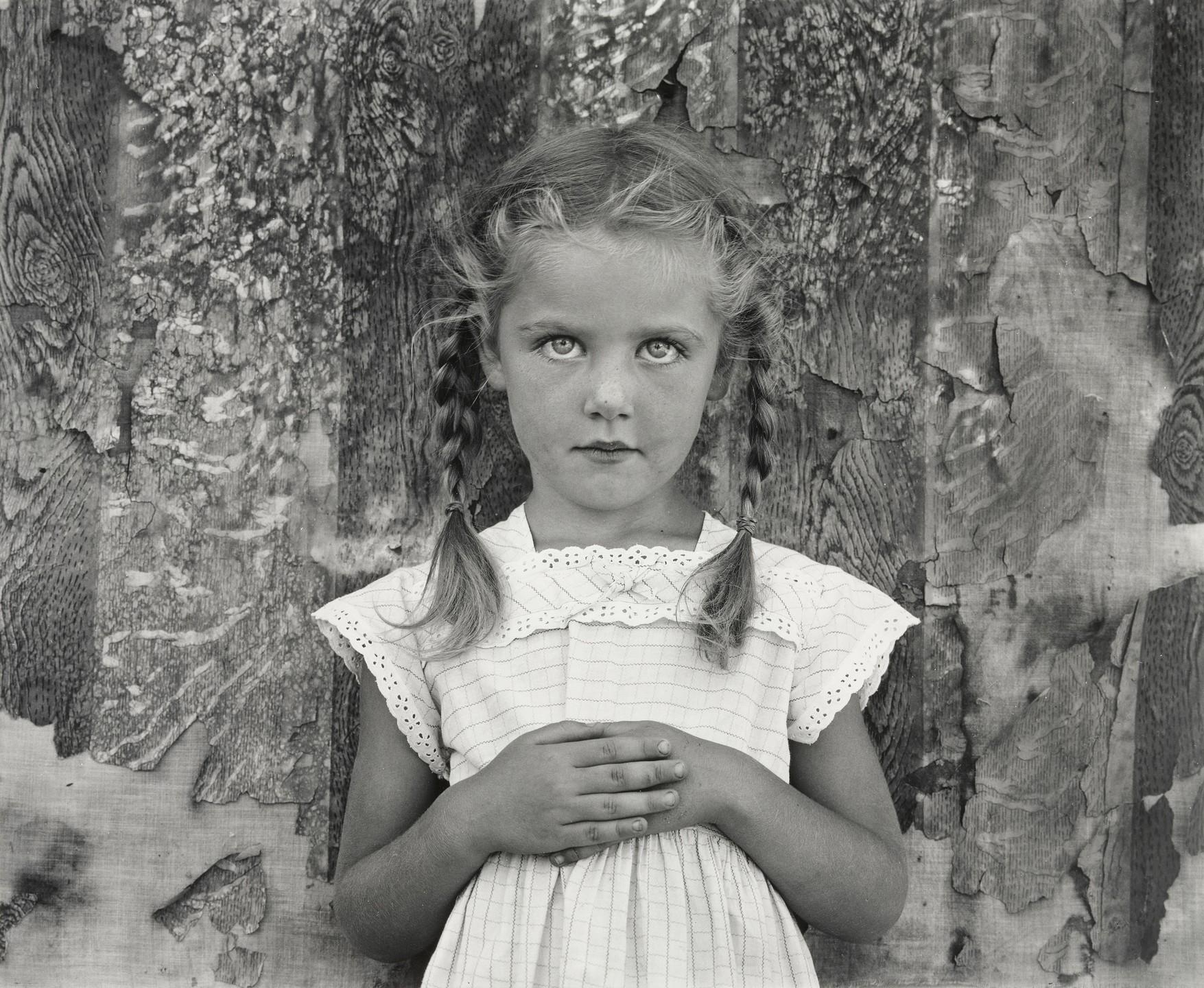 Foto em preto de branco do fotógrafo Frederick Sommer, intitulada Livia. A imagem apresenta uma menina branca, loira e de olhos claros, e possui no máximo sete anos. Seu cabelo está dividido em duas tranças, ela usa um vestido branco com orlas de renda, as mãos juntas em cima da barriga. Ela está encostada em uma parede de madeira descascada, e olha diretamente para a câmera.