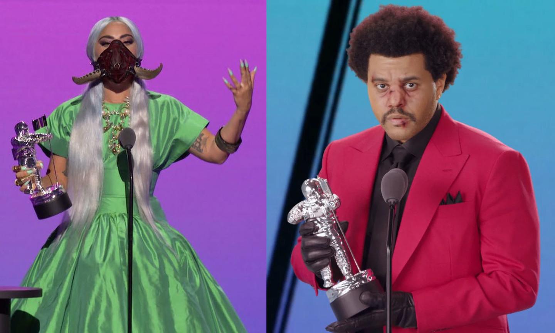 Descrição: Do lado esquerdo, a cantora Lady Gaga - aparece com um vestido verde de tafetá de seda, máscara exótica vermelha queimada/preta com dois chifres, com o cabelo platinado, longo e praticamente liso, ela também tem como acessórios: diversos anéis dourados, um bracelete no braço esquerdo e colares dourados - segurando com a mão direita um dos seus 5 prêmios no VMA 2020. Do lado direito, o cantor The Weeknd usando blazer vermelho, camisa, gravata e luvas pretas; cabelo crespo com penteado black, rosto maquiado com alguns ferimentos na área da boca e nariz. Ele segura o prêmio do VMA com as duas mãos pendendo para o seu lado direito.