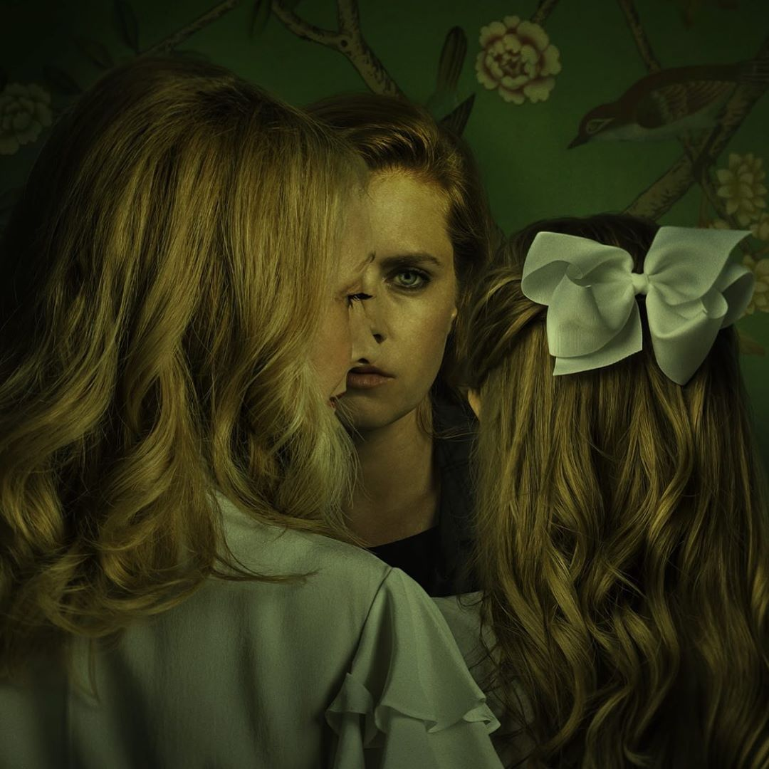 Foto promocional da série da HBO, adaptação de Objetos Cortantes. A foto possui um filtro amarelado quase sujo. Amy Adams, que interpreta Camille, é uma mulher ruiva, de olhos claros, e está usando uma maquiagem escura nos olhos e roupa preta. Está encostada na parede, coberta por um papel verde estampado por flores. À sua frente está Adora, interpretada por Patricia Clarkson, na esquerda, cobrindo o lado correspondente do corpo de Amy. Ela é uma mulher branca e loira, e está vestida de branco, de costas para a câmera, mas olha diretamente para Eliza Scanlen a sua direita, uma jovem branca e com os cabelos loiros presos parcialmente em um laço branco. Eliza interpreta Amma, e está de costas, cabeça baixa na direção de Amy.