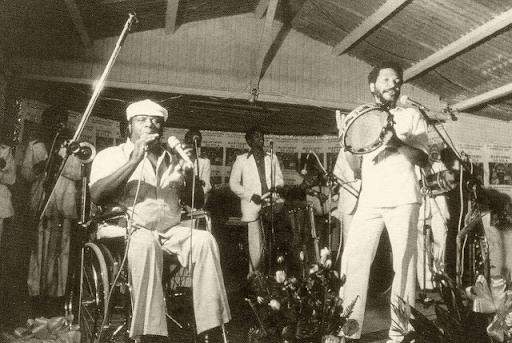 Uma fotografia em preto e branco mostra dois artistas consagrados do samba de raiz em um palco, tocando juntos. Ao lado esquerdo, temos Mestre Candeia sentado em uma cadeira de rodas, enquanto o mesmo segura dois microfones. À direita, Martinho da Vila, em pé, tocando um pandeiro, enquanto canta ao microfone. Ao fundo, percebemos outros instrumentos musicais e outras seis pessoas que também figuram na imagem, porém em segundo plano.
