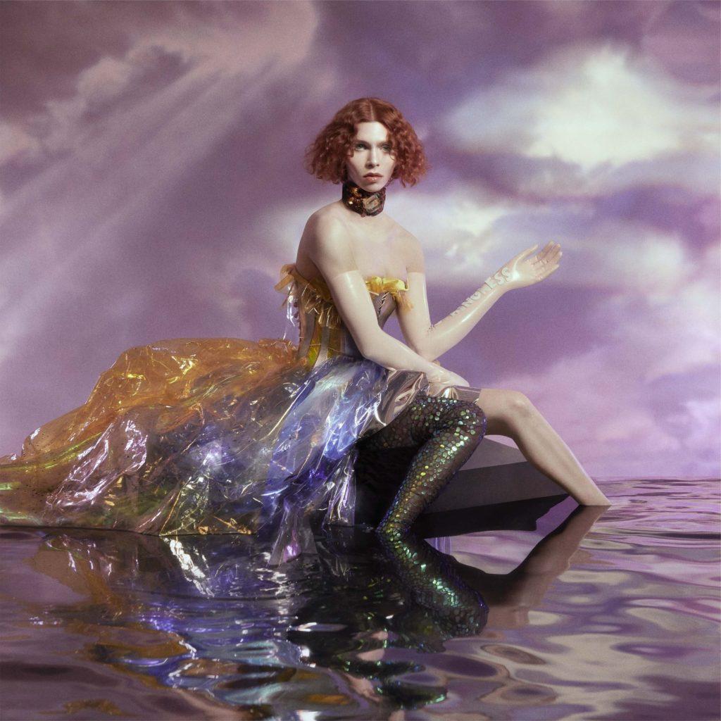 Capa do CD OIL OF EVERY PEARL'S UN-INSIDES. A imagem mostra SOPHIE em primeiro plano. Ela é uma mulher branca de cabelo curto ruivo. Ela veste um vestido de plástico na cor laranja e roxa. Seu pés estão dentro d'água e ela está sentada em uma plataforma. Ao fundo, foram adicionadas nuvens na cor roxa.