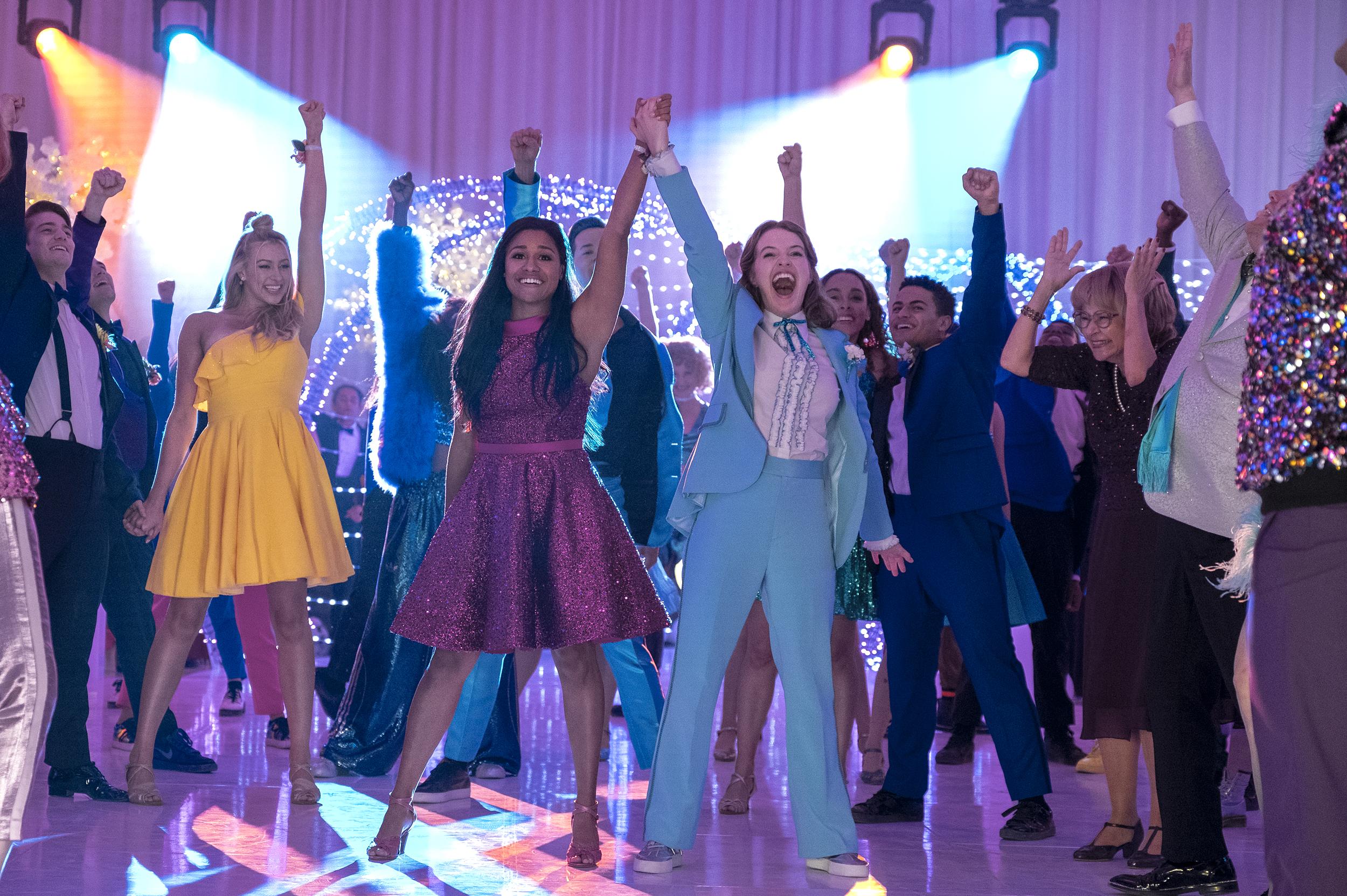 Cena do filme A Festa de Formatura. Mostra vários personagens no meio de uma pista de dança com os braços para cima. Ao centro as personagens Alyssa, de vestido roxo e cabelos pretos soltos, e Emma, de terno azul e cabelos ruivos soltos, erguem suas mãos unidas.