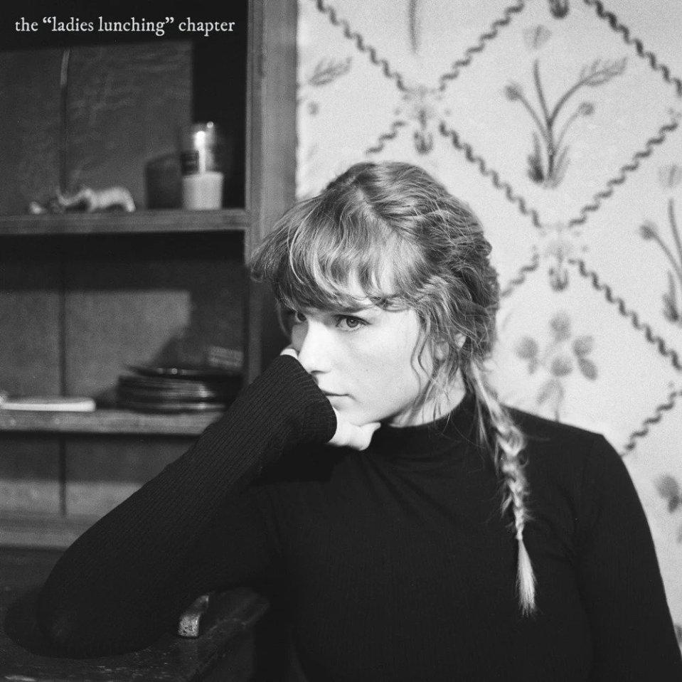 """Capa do EP the """"ladies lunching"""" chapter. Mostra Taylor Swift sentada e apoiando o cotovelo direito sobre uma mesa, e mão segurando seu rosto. Ela é uma mulher branca e tem os cabelos loiros trançados. Ela usa uma blusa de manga comprida preta. Ao topo da imagem está escrito the """"ladies lunching"""" chapter em cinza. A imagem é em preto e branco."""