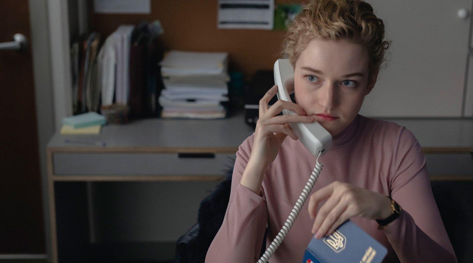 A imagem é uma cena do filme A Assistente. Nela, está a atriz Julia Garner, que interpreta a personagem Jane. Jane é uma mulher branca, de olhos azuis, cabelos loiros e amarrados em um coque, ela veste uma blusa rosa de gola alta e mangas compridas e usa um relógio preto em seu pulso esquerdo. Na cena, Jane está no escritório do trabalho sentada em uma cadeira, é possível ver da sua cintura para cima. Ela está falando a um telefone branco com fio, segurando-o com sua mão direita, e está com o que parece ser um passaporte em sua mão esquerda. Ela olha fixamente para o lado direito, com um olhar de preocupação.