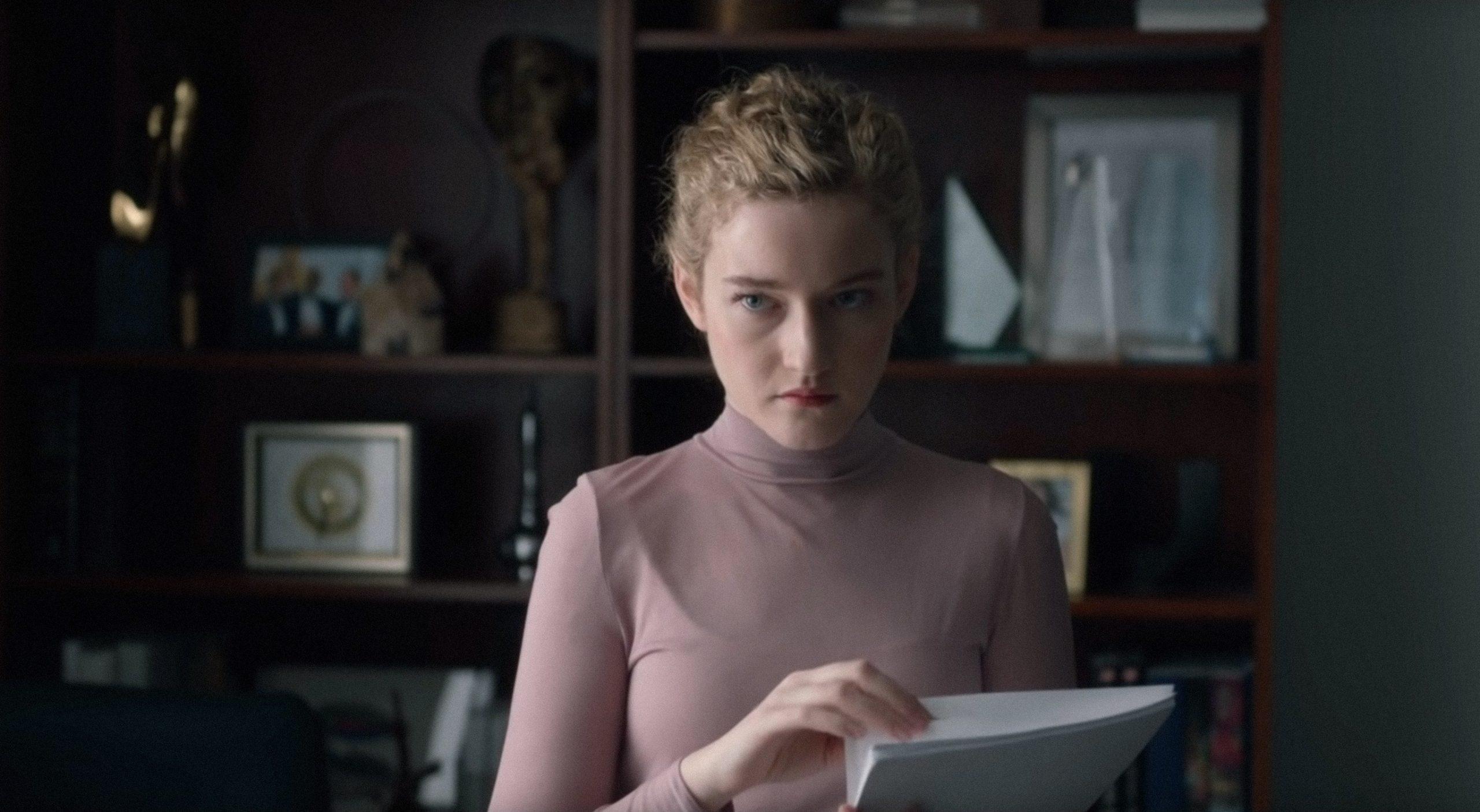 A imagem é de uma cena do filme A Assistente. Nela, a atriz Julia Garner, que interpreta Jane, está segurando um roteiro no braço esquerdo, com a mão direita puxando uma das folhas. Julia é uma mulher branca de cabelos loiros, que estão presos em um coque, ela veste uma blusa rosa de mangas compridas e gola alta e está olhando fixamente para a sua direita. Atrás de Julia, há uma estante com troféus, livros e enfeites.