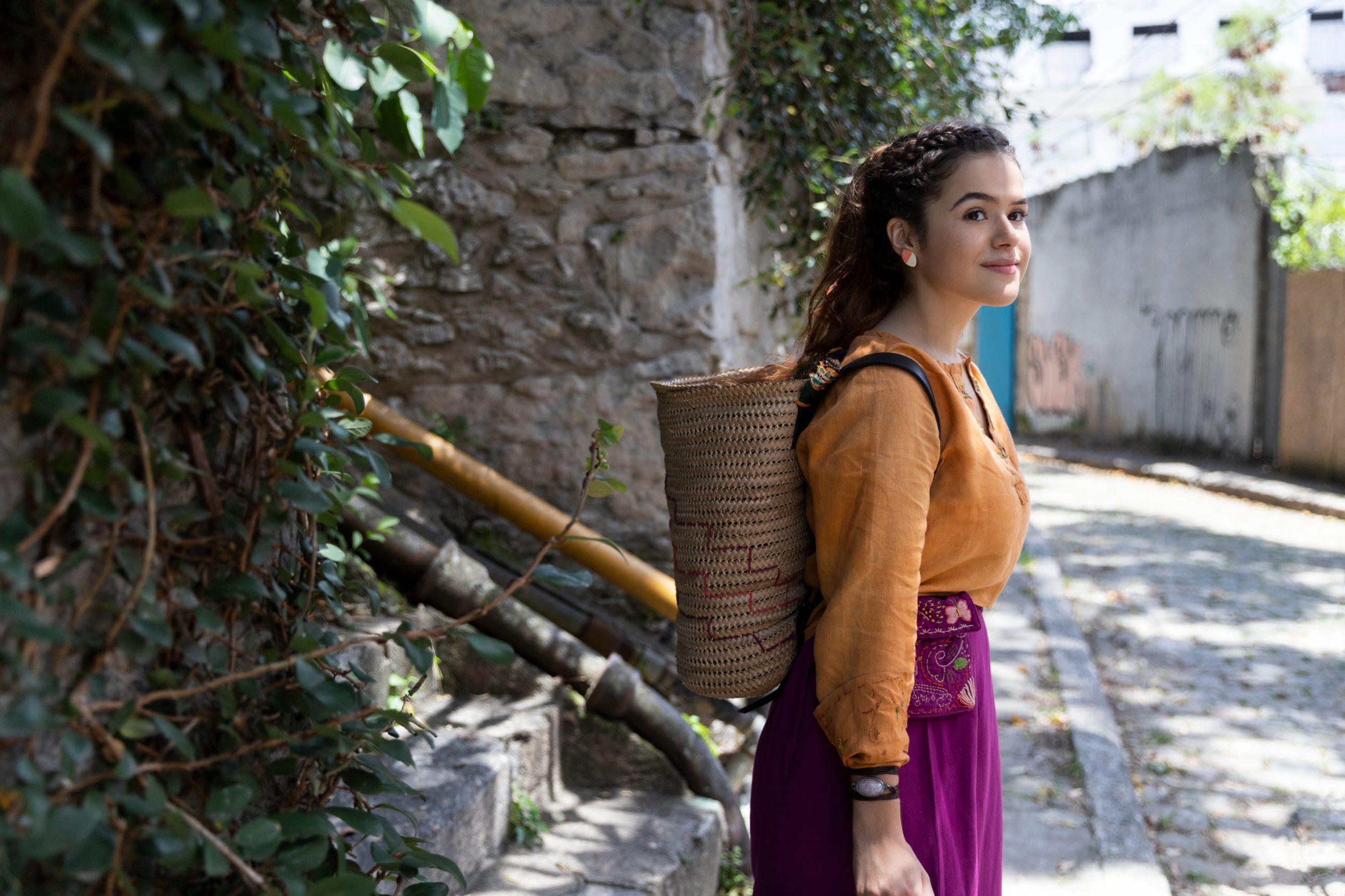 Cena do filme Pai em Dobro. Mostra a personagem de Maísa Silva caracterizada como Vicenza. Ela é uma mulher branca, jovem e usa uma blusa laranja, de mangas compridas e soltas, que está colocada para dentro de uma calça pantalona de cintura alta e roxa. Ela tem os cabelos castanhos presos em várias tranças que se unem no topo da cabeça e usa uma mochila de palha. Ela está de perfil em uma rua e ao fundo vemos algumas paredes cinzas e alguns galhos com folhas.