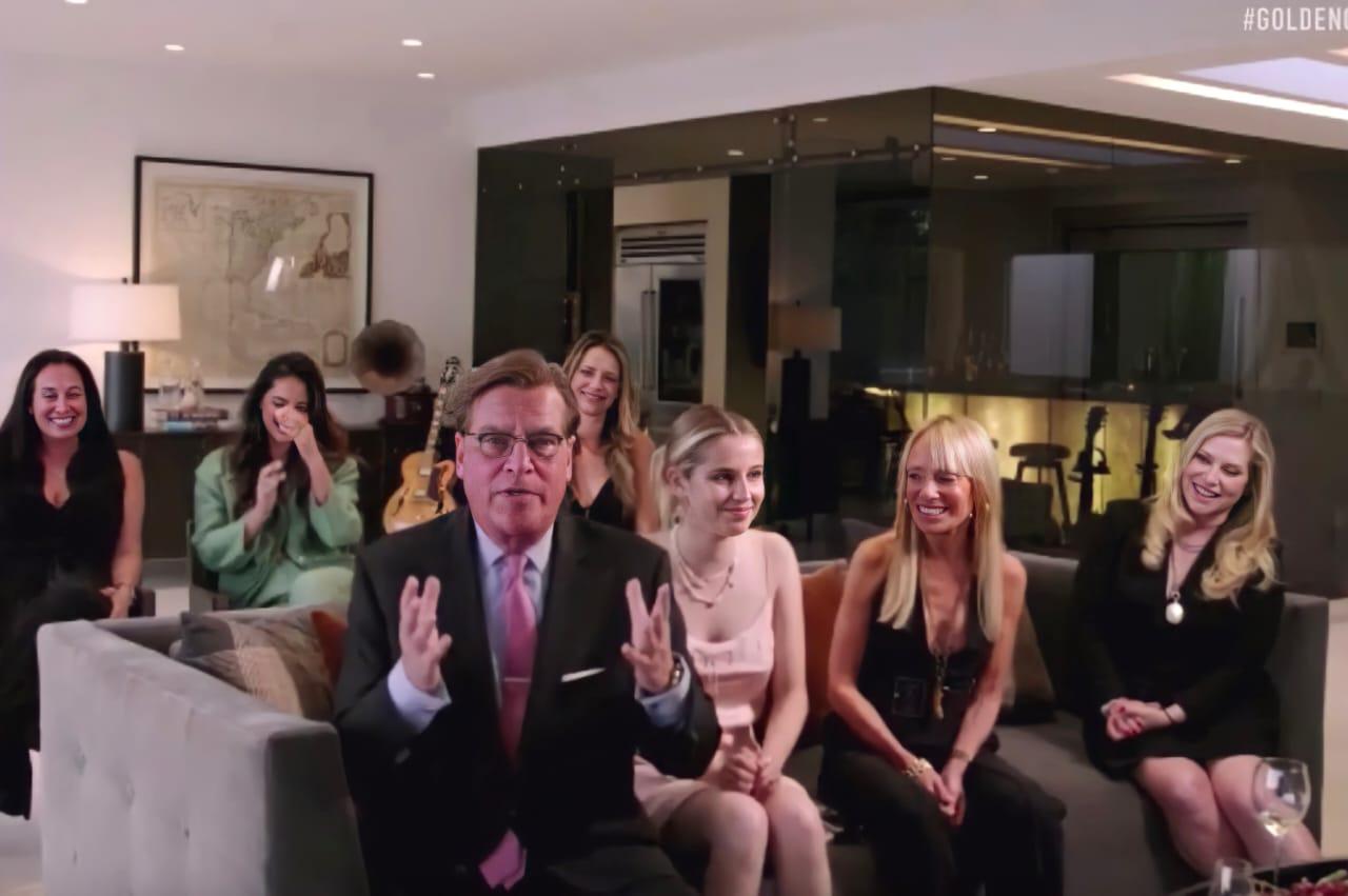 Foto do diretor Aaron Sorkin. Em uma sala clara, Aaron está sentado na ponta do sofá. É um homem branco vestindo um terno preto, blusa azul e gravata rosa. Ao seu redor, há seis mulheres brancas, três sentadas no sofá com ele e o resto em cadeiras atrás dele. No fundo é possível ver um quadro, e alguns instrumentos musicais.