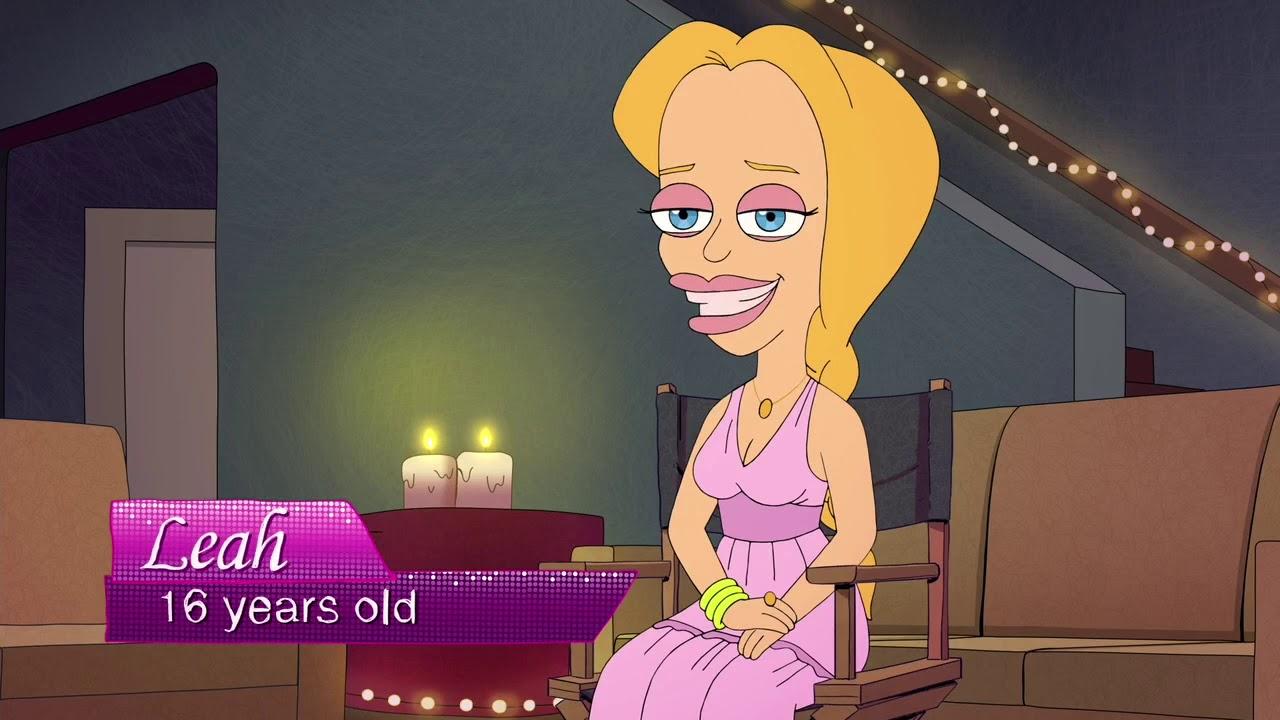 Cena da sitcom animada Big Mouth em sua segunda temporada. O cenário ao fundo da imagem é uma sala de estar com dois sofás marrons, uma mesa com velas localizadas ao centro e uma escada no canto direito da imagem. Em primeiro plano, no centro da imagem, está a personagem Leah. Ela está sentada em uma cadeira e virada ¾ para a frente da câmera. A personagem é desenhada com traços exagerados ao estilo cartoon, ela é branca, tem o cabelo loiro e liso preso em trança, olhos azuis, está usando um vestido rosa claro com um colar e anel dourados e uma pulseira amarela.