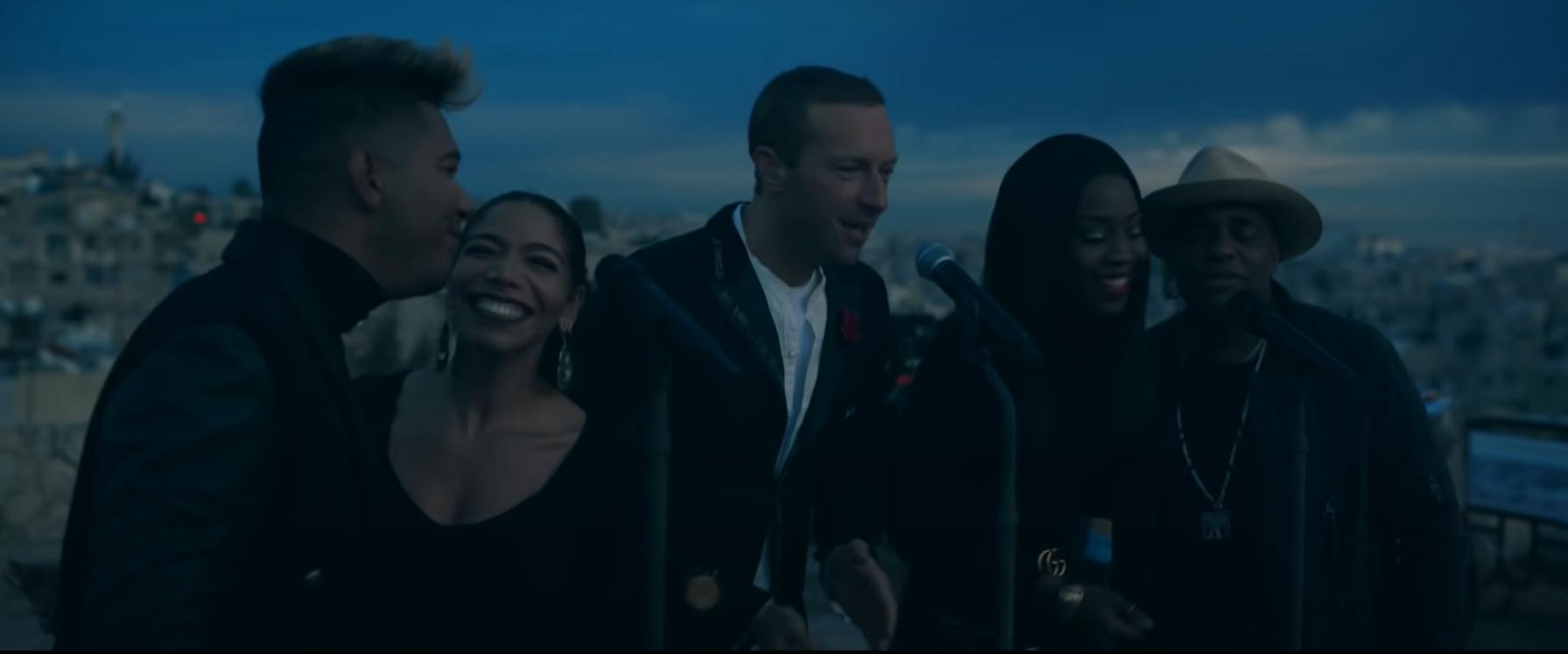 Imagem da apresentação que Coldplay fez ao vivo do disco Everyday Life. Na fotografia, o vocalista Chris Martin está ao centro, na frente de um microfone, cantando. Ao lado esquerdo dele, estão dois cantores, primeiro, à esquerda da imagem, um homem negro de cabelo liso e logo depois uma mulher, também negra, de cabelos presos, batom escuro e sorridente. Eles dividem um microfone, que está logo na frente deles. Então, à direita de Chris Martin, estão mais outros dois cantores. Primeiro, uma mulher negra, de cabelos lisos soltos, e depois, na extremidade direita da imagem, um homem, que usa um chapéu marrom. Eles também dividem um microfone e sorriem enquanto cantam. Ao fundo da imagem, está a cidade e o céu, ainda meio escuro por conta do amanhecer.