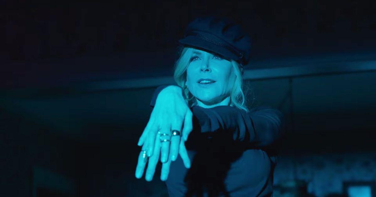 Cena do filme A Festa de Formatura, mostra Nicole Kidman com as mãos uma em cima da outra, estendidas a frente do corpo. Ela usa uma boina e blusa de mangas compridas, ambos pretos, tem os cabelos loiros presos com a franja solta na fente do rosto. Ela é uma mulher branca e está sendo iluminada por uma luz azul.