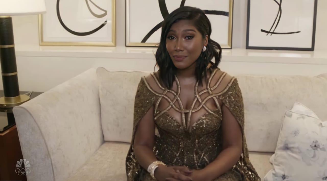 Taylor Simone Ledward, uma mulher negra, está sentada em um sofá branco, vestindo um vestido dourado escuro, Seu cabelo preto está na altura do ombro, e ela olha para câmera com um olhar emocionado. Atrás dela, quadros brancos com riscos pretos estão pendurados.
