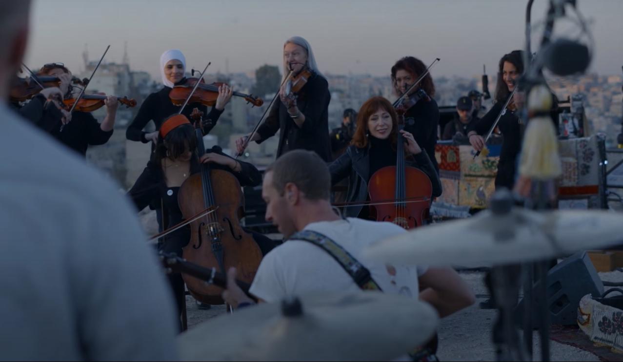 Imagem da apresentação que Coldplay fez ao vivo do disco Everyday Life. Na fotografia, observamos uma orquestra de cordas de mulheres de diversas etnias e religiões. Em segundo plano, levemente desfocado na metade inferior da imagem, está Chris Martin, de costas para a câmera, ajoelhado no chão enquanto toca violão. Atrás dele, mais à frente da imagem, ainda desfocado, podemos observar a bateria de Will Champion. A foto é colorida em tons suaves, demonstrando o fim do pôr do sol.
