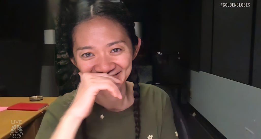Foto da diretora e roteirista Chloé Zhao. Uma mulher asiática, de cabelos longos e pretos, amarrados em uma trança. Ela veste uma roupa verde escura. Sua mão esquerda está apoiando sua cabeça na altura da boca. À esquerda vemos uma mesa marrom com um caderno vermelho