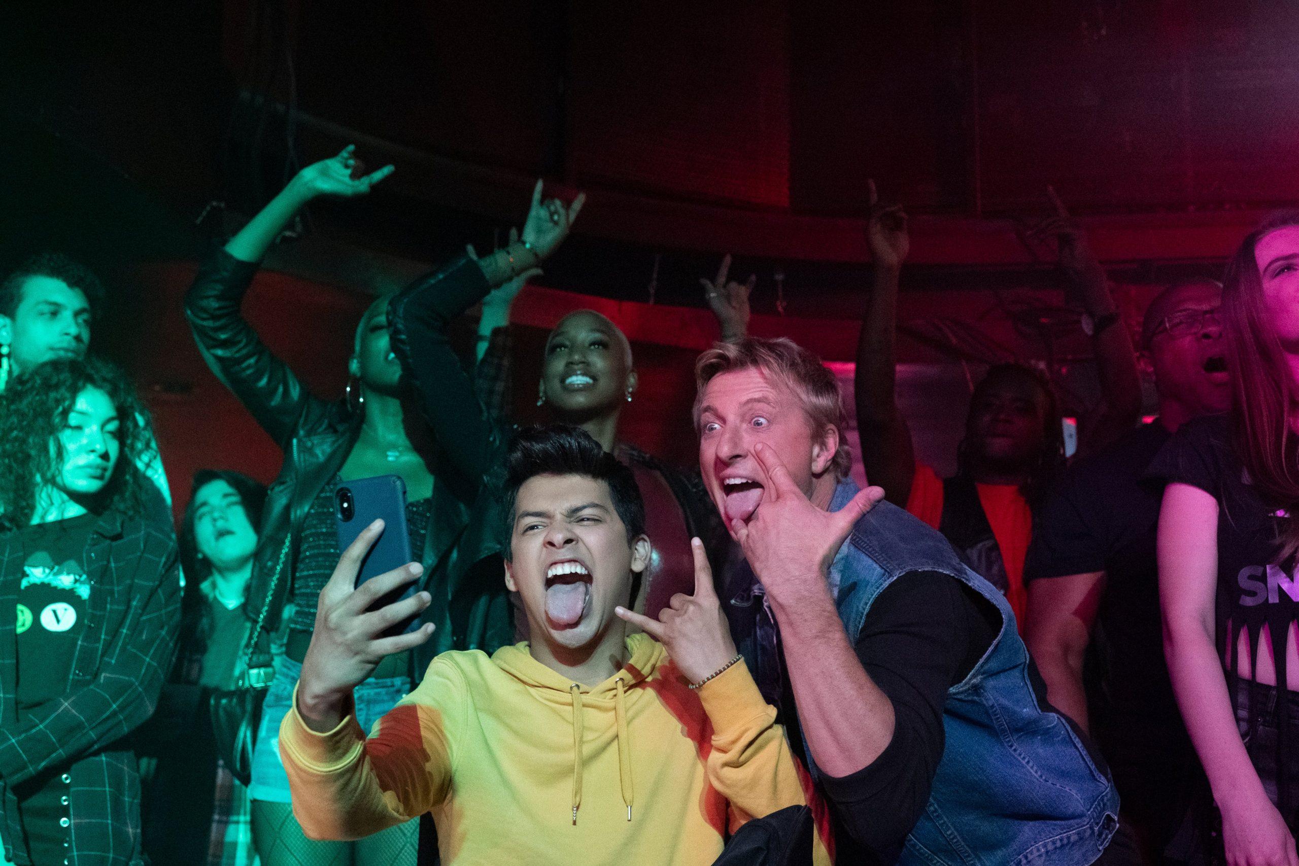 Dois amigos ao centro tirando uma selfie, fazendo sinal de rock n' roll com as mãos e mostrando a língua. Ao fundo, um grupo de pessoas aproveitando um show de música