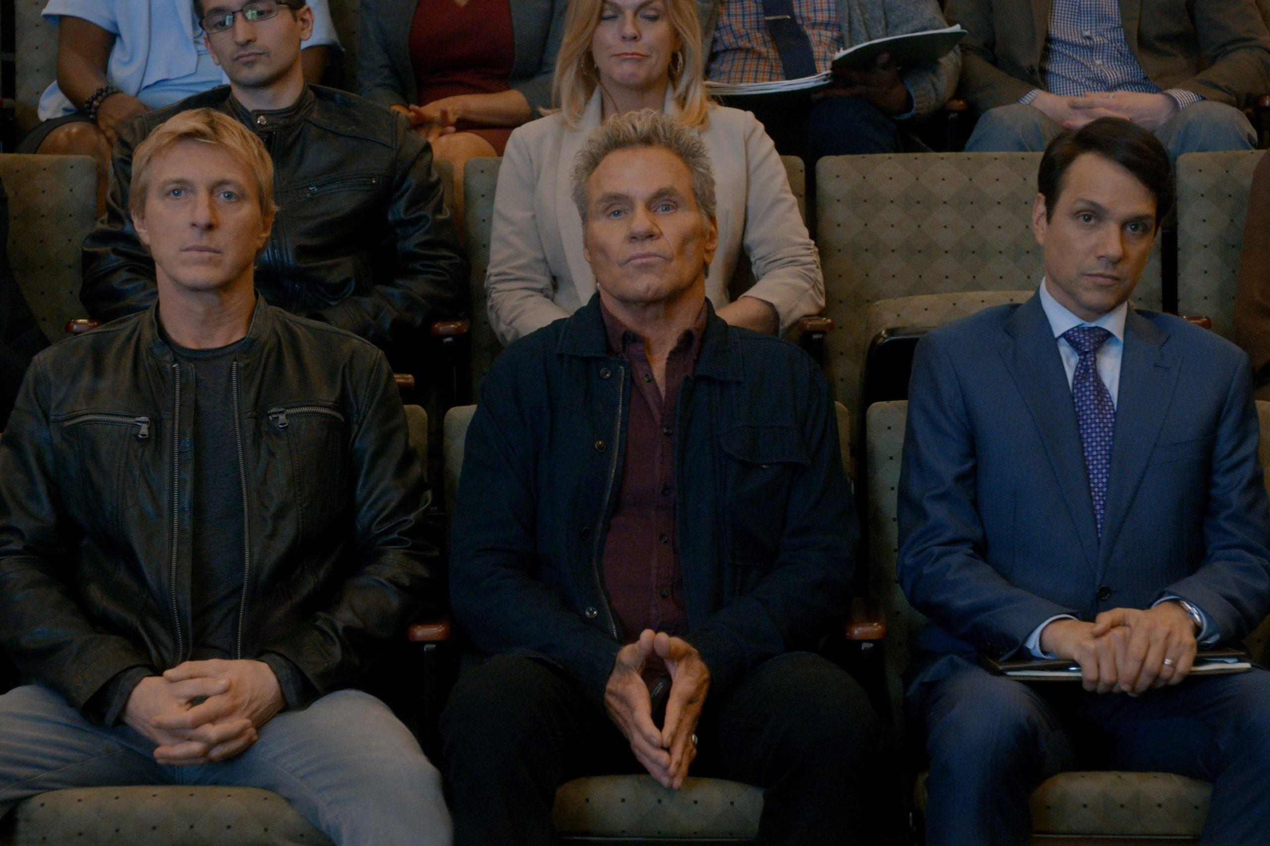 Adultos sentados nas cadeiras de um auditório, olhando para a frente