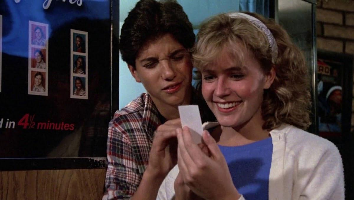 Dois adolescentes com vestimentas típicas dos anos 80, olhando uma foto de cabine fotográfica. Ao fundo, uma cabine fotográfica.