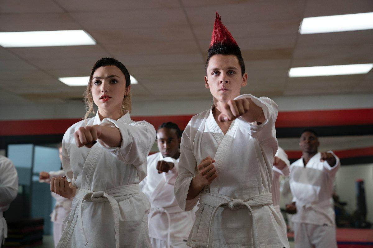 À frente, dois adolescentes praticando karatê de uniforme branco. Ao fundo, outros alunos imitando-os.