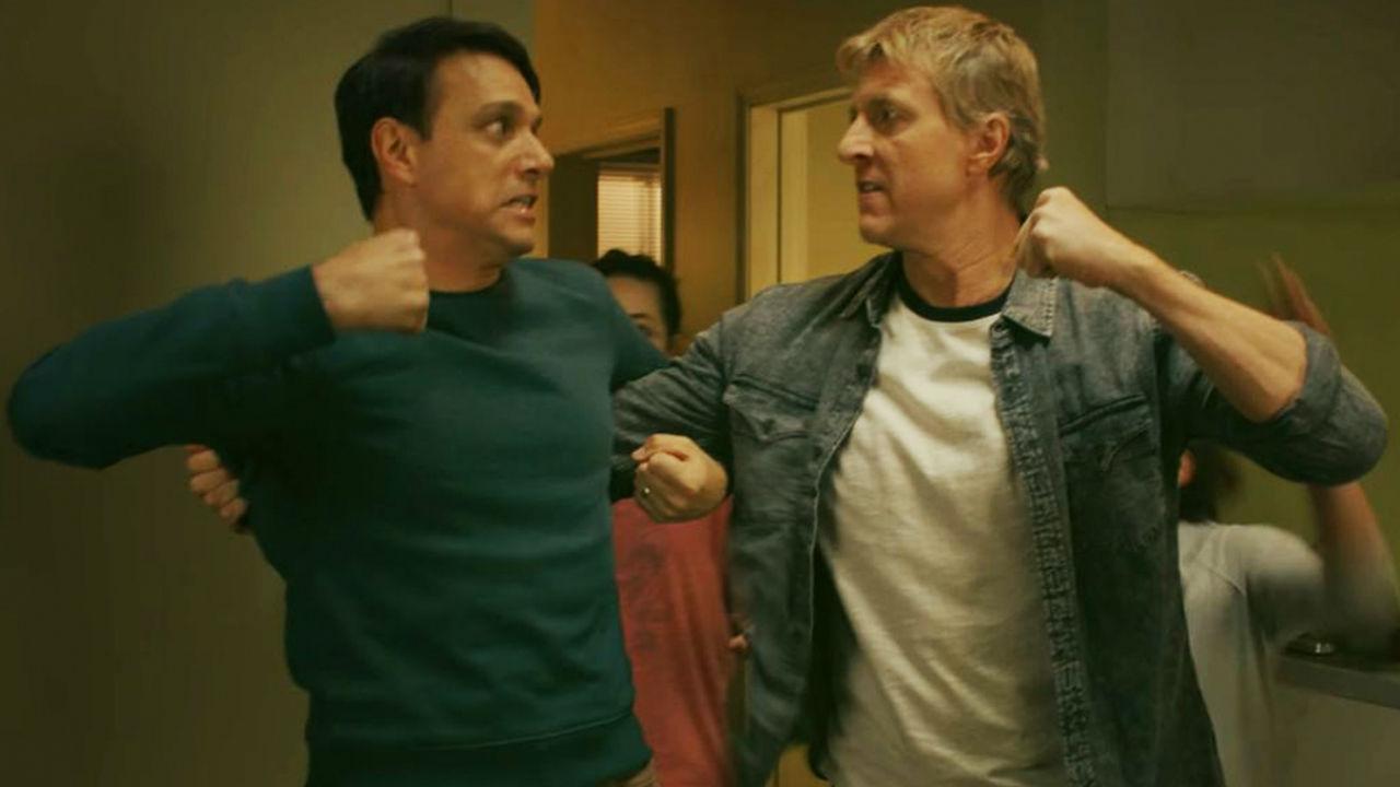 Dois adultos mostrando o punho um para o outro, insinuando uma briga.