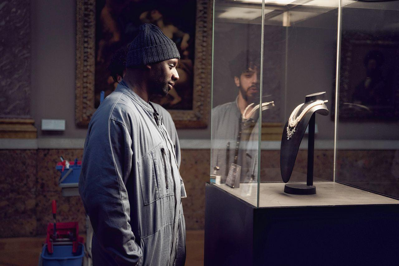 Cena da série Lupin, da Netflix. Nela vemos Assane, um homem negro usando casacos e touca observa colar exposto em museu.